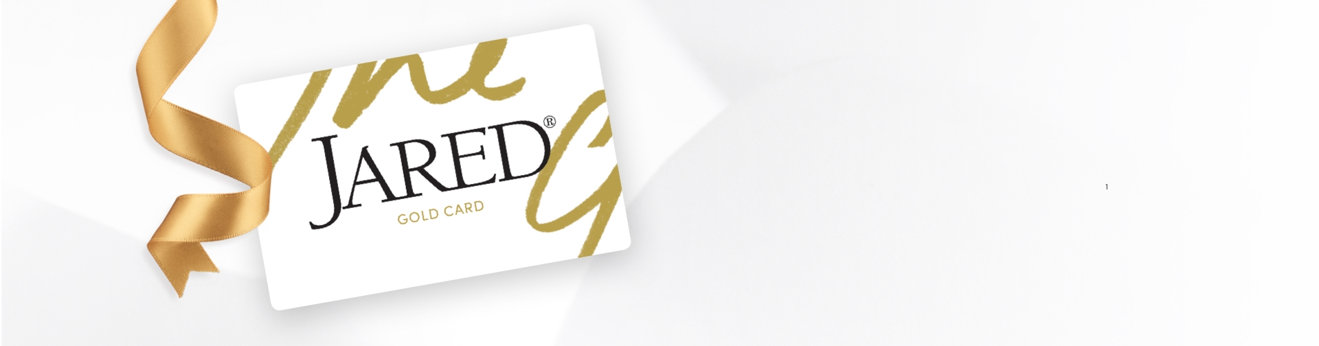 Jared Gold Credit Card on a grey background and a gold ribbon.