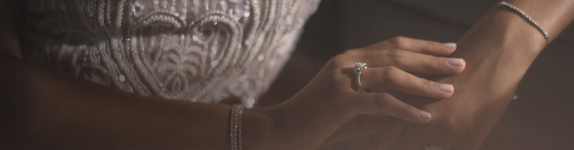 Woman wearing luxury diamond jewelry including multiple diamond tennis bracelets and diamond engagement ring.
