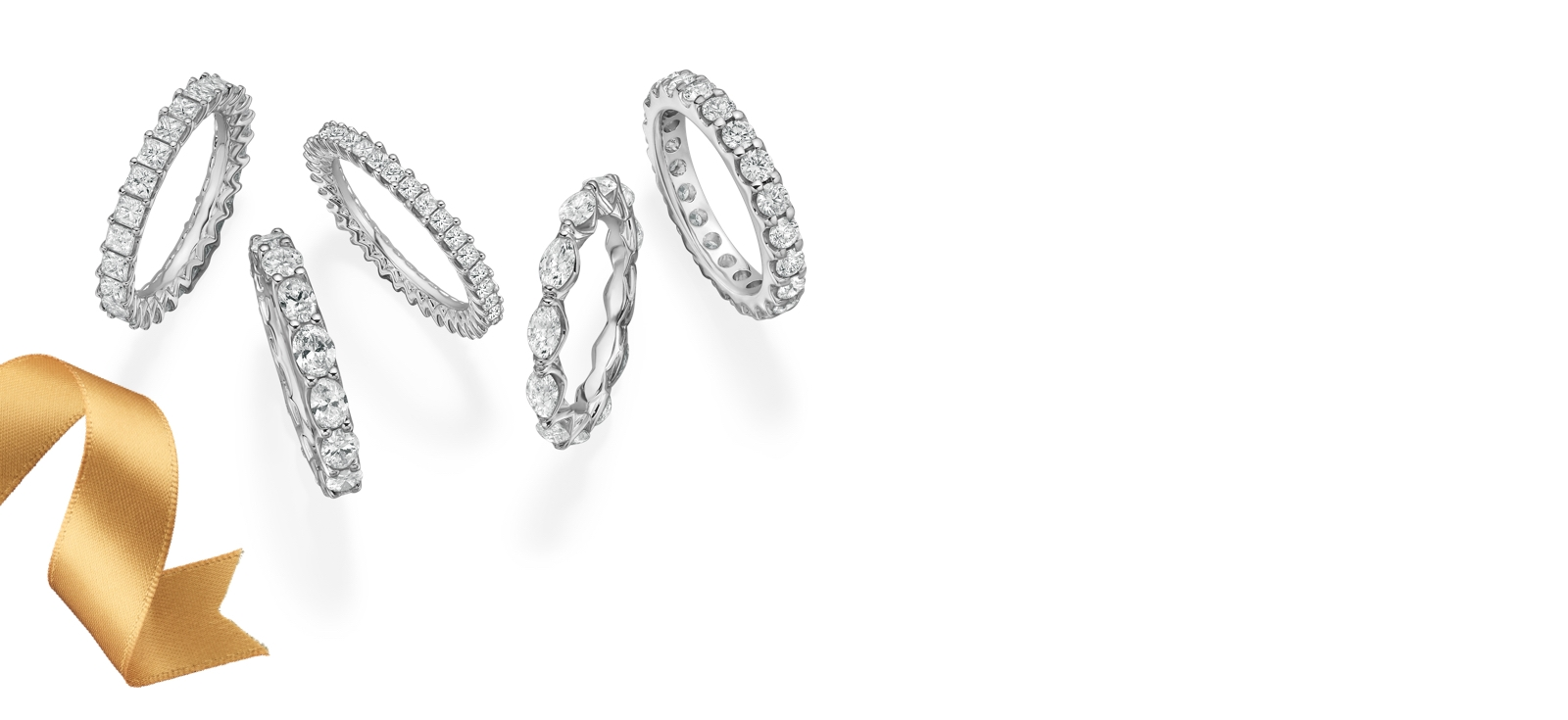 Five diamond eternity bands with princess, round, marquise, emerald and cushion cut diamonds set in white gold on a white background and a gold ribbon.