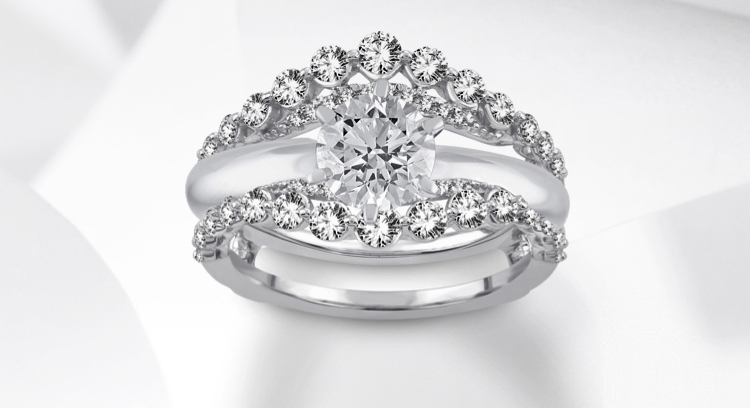 White gold diamond wrap enhancer rings on a white gold engagement ring on a grey background.