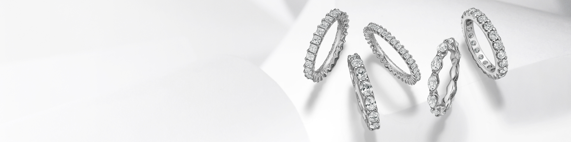 White gold diamond eternity bands on a grey background.