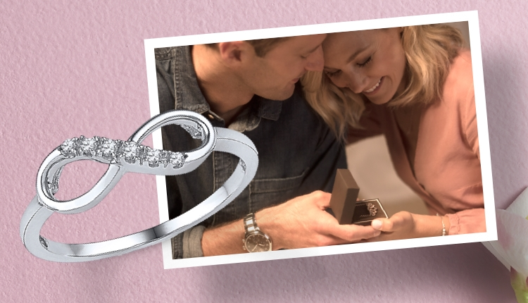 Man giving a woman an anniversary gift with an image of a white gold and diamond infinity ring on a pink background with flowers.