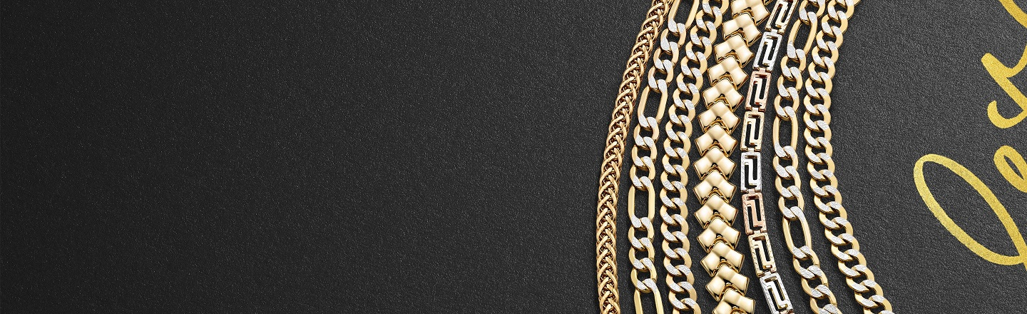 Multiple chain necklace in yellow gold and mixed gold tones in different chain types on a black textured background.