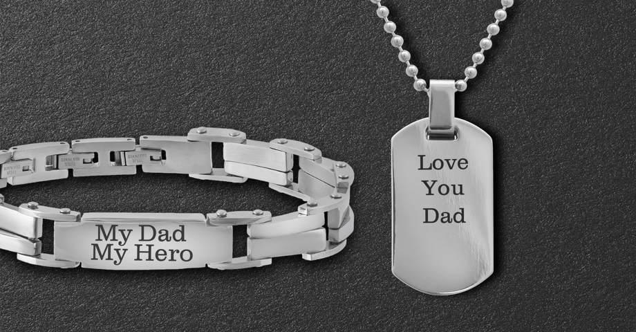 A bracelet that says My Dad My Hero and a dog tag necklace that says Love you Dad on a black textured background.