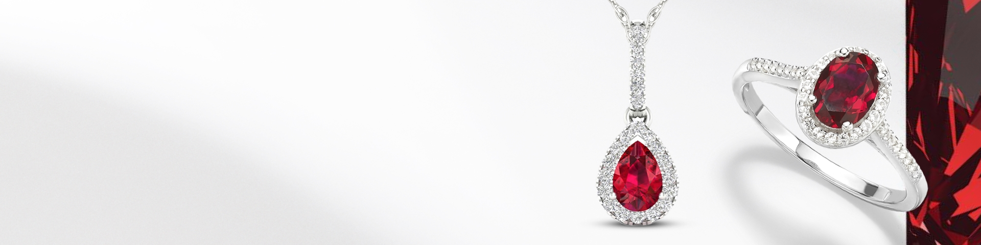 Ruby ring and necklace set in white gold with diamond halos on a white bckground and red gemstone texture.