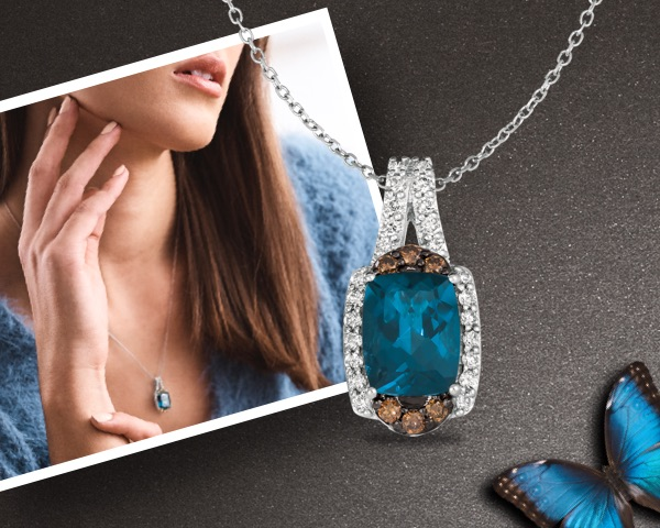 Image of a woman wearing a Le Vian sapphire necklace from Jared on a grey textured background.
