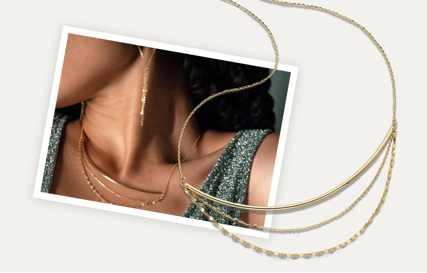 Woman wearing gold necklace and earrings featuring a gold layered necklace. Shop gold jewelry at Jared.