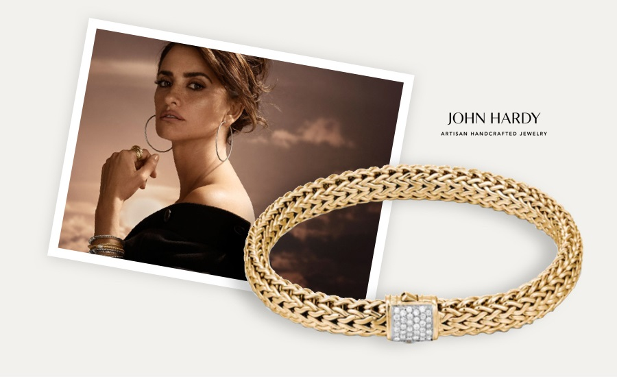 Woman wearing layered John Hardy chain bracelets and gold hoop earrings. Shop John Hardy jewelry at Jared.