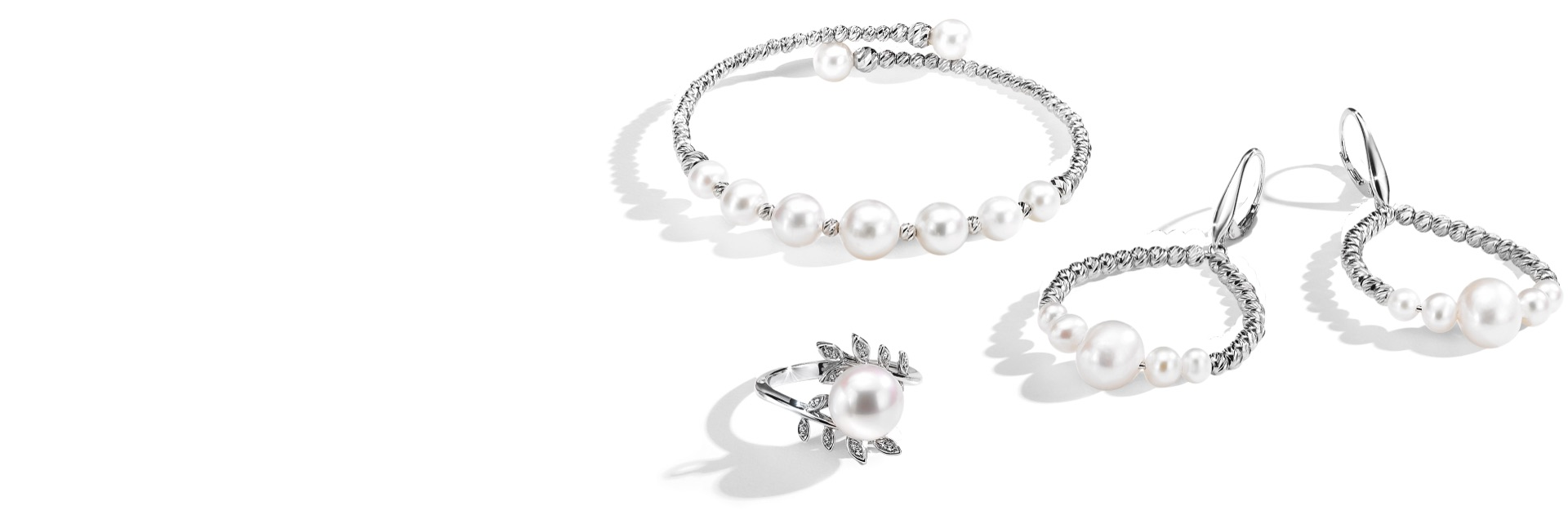 Cultured pearl bracelet, earrings and ring in textured settings from Jared on a white background.