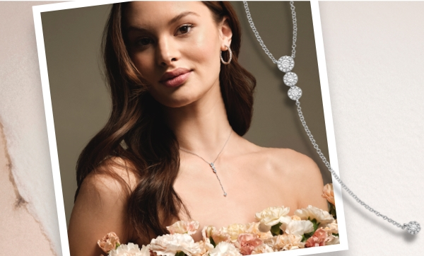 Woman wearing new Shy Creation diamond hoop earrings and a drop diamond necklace from Jared and holding flowers.
