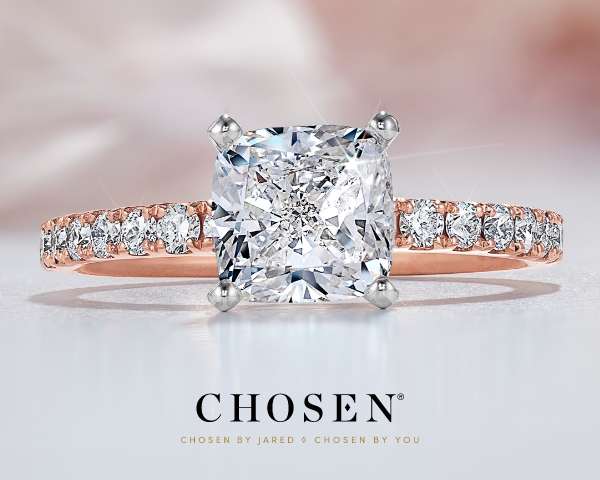 Chosen engagement ring on a pink floral background.