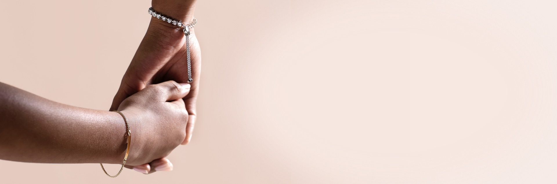 Mother and child holding hands wearing bracelets from Jared with a soft pink background.