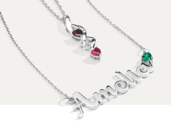 Two personalized birthstone necklaces from Jared on a light grey background.