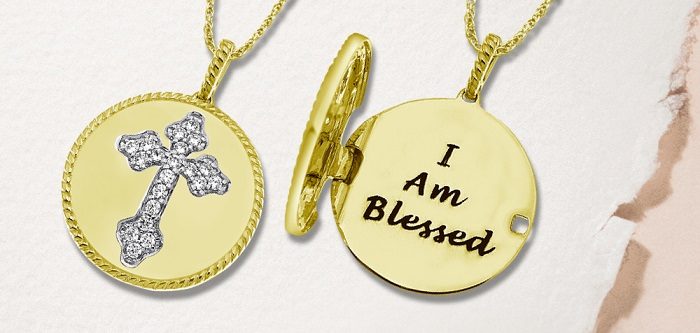 Yellow gold locket necklace with diamond cross imbedded and I am Blessed message engraved inside on a pink and white paper background.
