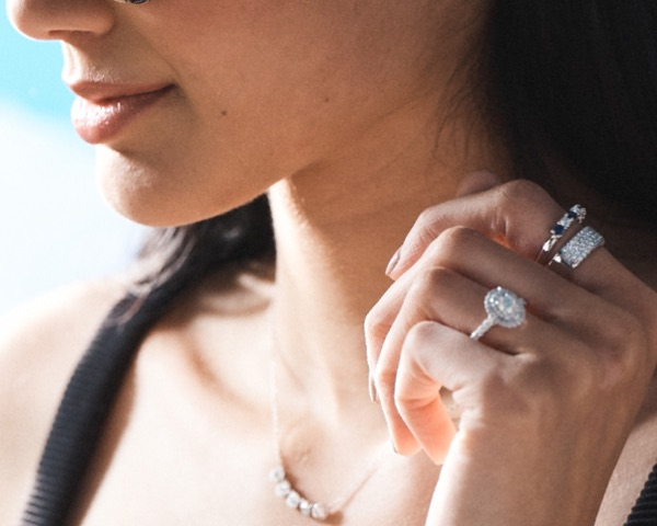 profile of woman with stacked rings on hand