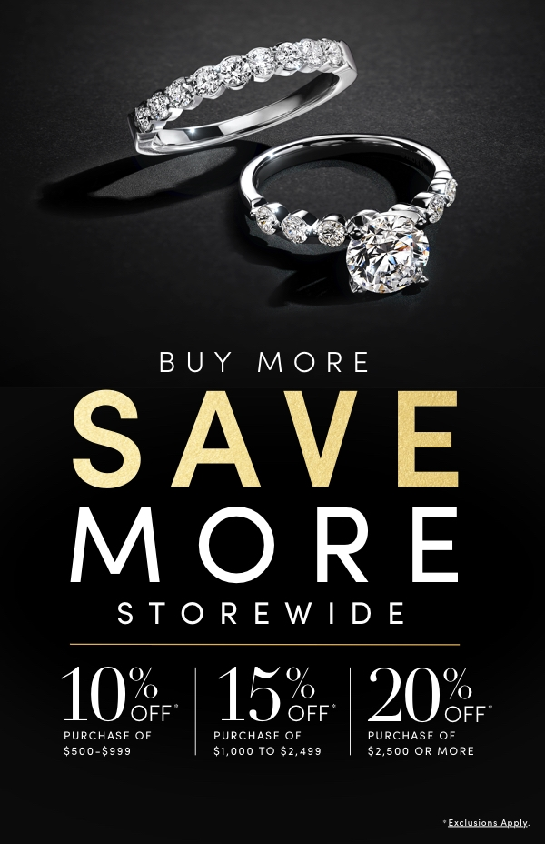 Photograph of an engagement ring and wedding bands on a black background. Buy More, Save More Storewide - April 1-April 11.