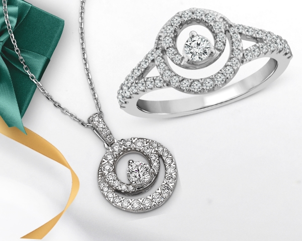 Closer Together diamond circle necklace and ring next to a gold ribbon and green gift box.