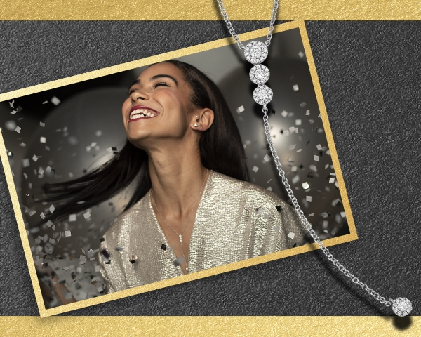 Woman wearing a 14K white gold and diamond lariat necklace on a black background, surrounded by confetti. Shop all New Year's jewelry.