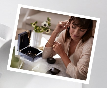 Woman sitting front of a black jewelry box looking at yellow gold pendants, earrings, bracelets and rings. Shop all WOLF jewelry boxes and watch winders.