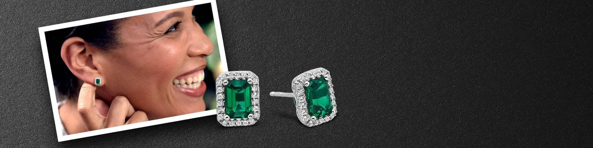 Emerald gemstone earrings rest against a portrait of a woman modeling the same pair of earrings.