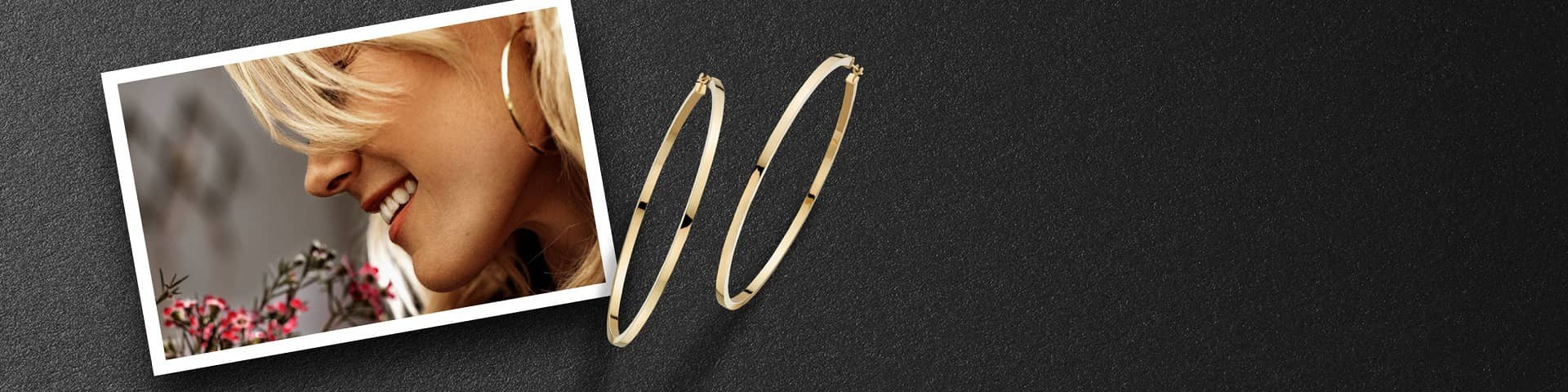 Gold hoop earrings rest against a portrait of a woman modeling the same pair of earrings.