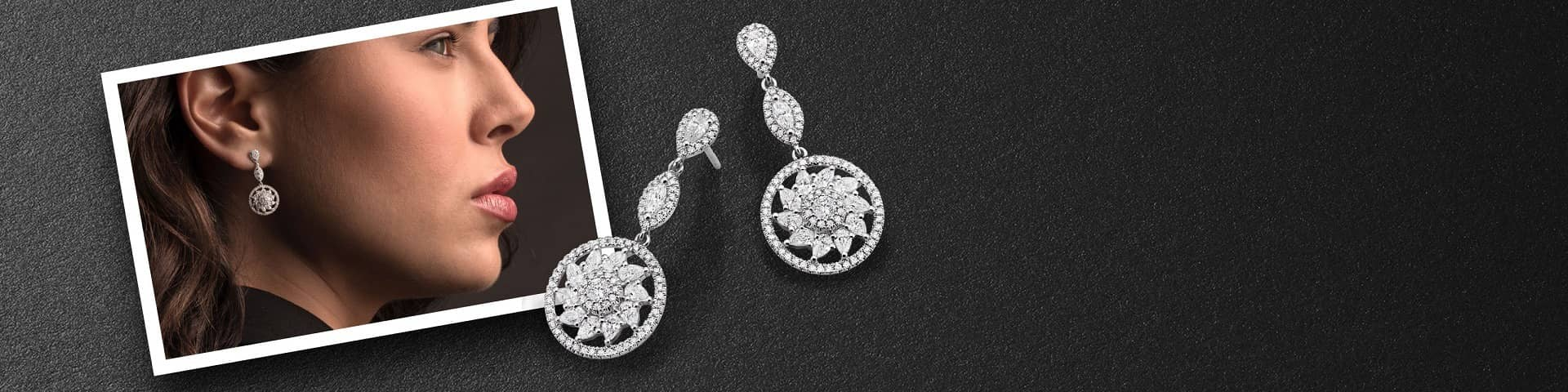 Diamond drop earrings rest against a portrait of a woman modeling the same pair of earrings.