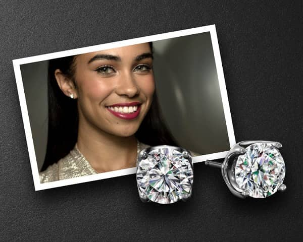 Diamond stud earrings rest against a portrait of a woman modeling the same pair of earrings.