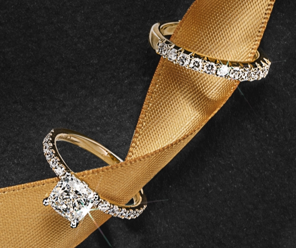 Engagement ring and wedding band entwined in gold ribbon