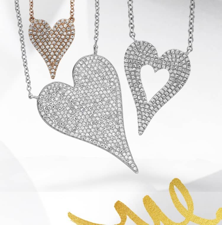 Three heart pendant necklaces hanging against a white background with a gold decorative swirl.